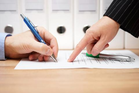 Photo: Thinkstock.com. Business woman is pointing where to sign on document.